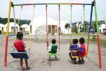 Image of children in a playground of a dome village.